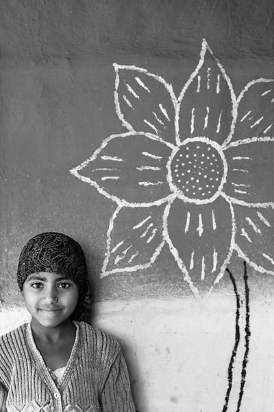 Girl by decorated village hut, North of Delhi