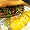 Patio BBQ Steak Sandwich on buttery hoagie roll with charred onion, cheddar, and grilled corn