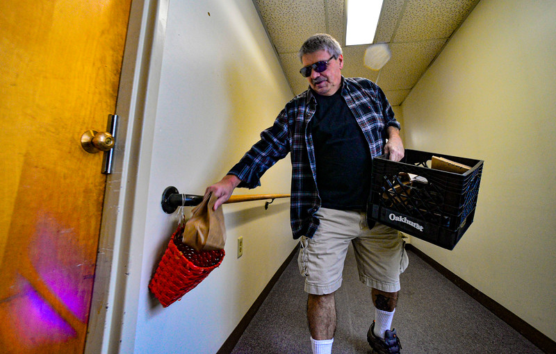 KRISTOPHER RADDER — BRATTLEBORO REFORMER<br /> Gino Butler puts meals into baskets that people left outside their doors at the Elliot Street Apartments, in Brattleboro, Vt., as the Brattleboro Senior Center adjusts services amid the COVID-19 outbreak on Thursday, March 19, 2020.