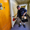 Gino Butler puts meals into baskets that people left outside their doors at the Elliot Street Apartments, in Brattleboro, Vt., as the Brattleboro Senior Center adjusts services amid the COVID-19 outbreak on Thursday, March 19, 2020. Kristopher Radder, Brattleboro Reformer via AP