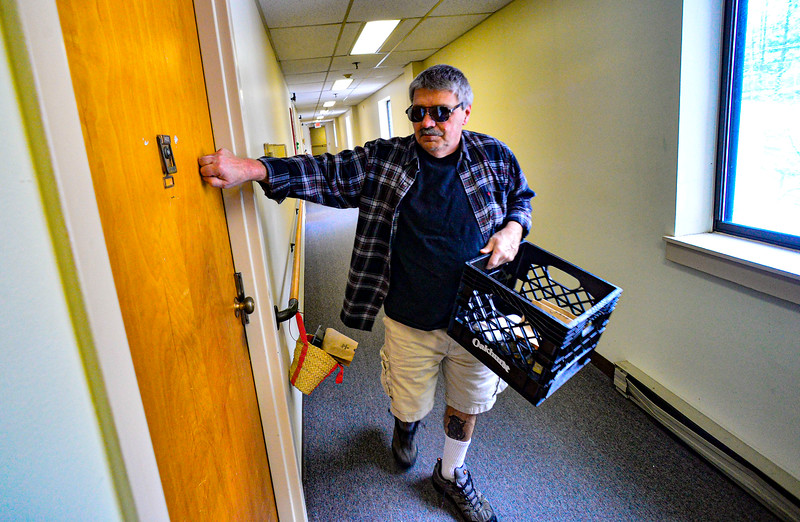 Gino Butler knocks on a resident's door after putting the meal into a basket that was left outside the door at the Elliot Street Apartments, in Brattleboro, Vt., as the Brattleboro Senior Center adjusts services amid the COVID-19 outbreak on Thursday, March 19, 2020. Kristopher Radder, Brattleboro Reformer via AP