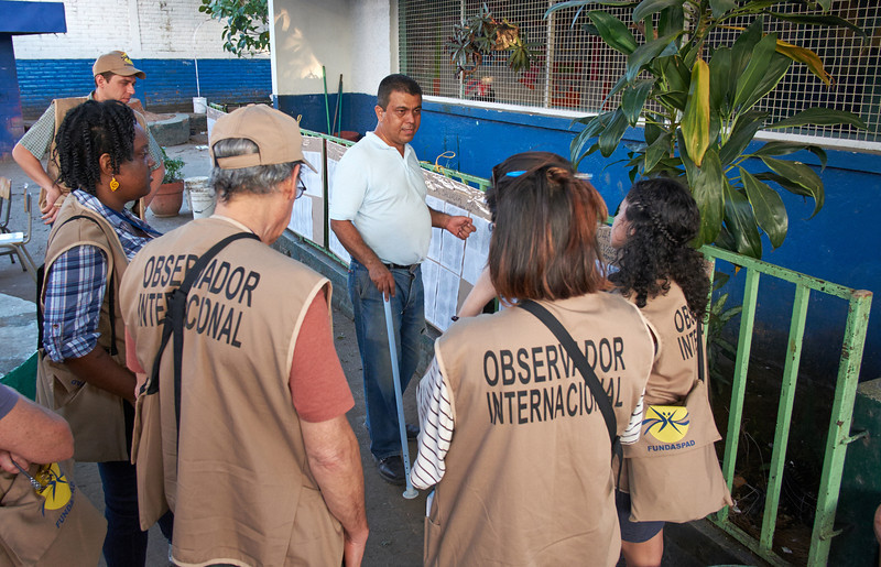 An election official in Santa Ana shows the pre-election preparations to the observers.