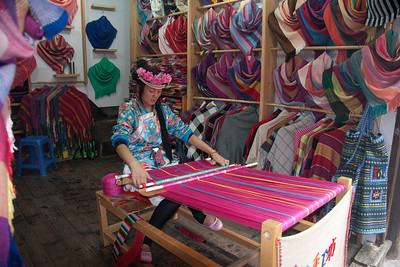Ethnic lady weaving colorful scarves and shawls that you see in the background.