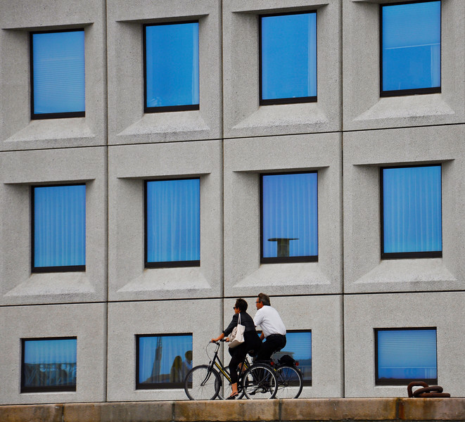 A couple rides their bicycles past Maersk HQ. 2010.