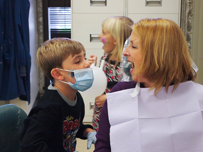 Boy plays dentist with his mom at a community health clinic.