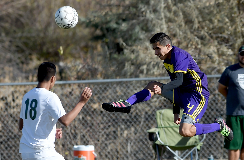 . Kevin Arriaga, right, of Denver North, flies in on a kick past Jonathan Jimenez Flores, of Niwot, at Niwot High School on Saturday. Cliff Grassmick  Photographer November 4, 2017