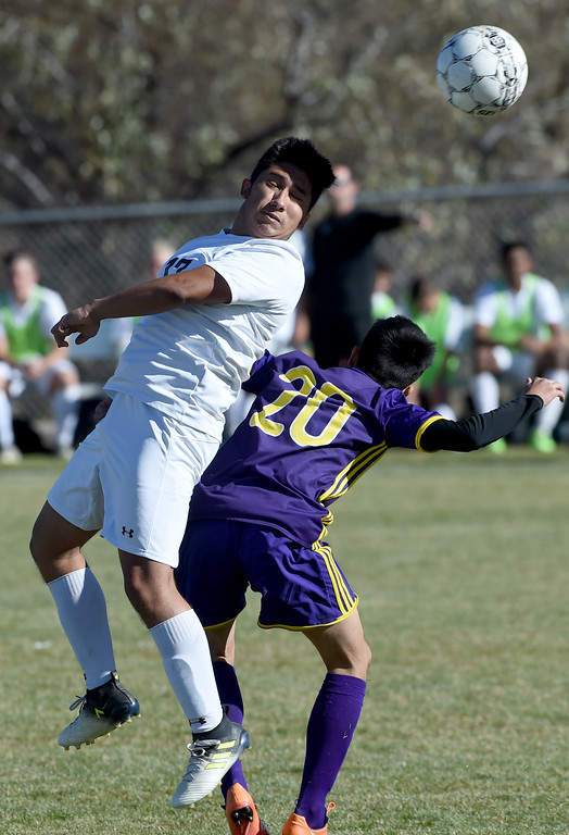 . Jesus Gonzales, left, of Niwot, connects on a header over Lorenzo Hernandez, of Denver North, at Niwot High School on Saturday. Cliff Grassmick  Photographer November 4, 2017