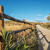 wooden fence with a shadow and a  bike trail  - Poudre River Trail in northern Colorado near Windsor
