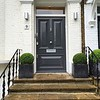 LONDON - MAY 18: Smart house entrance with grey front door and topiary bushes on May 18, 2016 in Ham