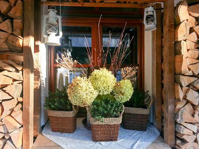 Abendsonne Blumenschmuck Ladenfenster Holzstoß Terrasse