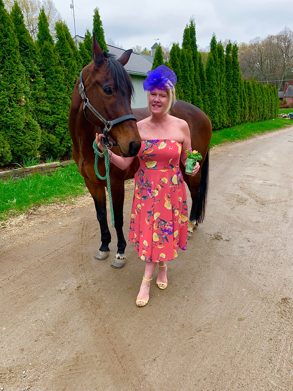 . Colby�s charm: Colby, this charming horse, runs strong to fight MS! Each year ,my sweet longtime friend from Chelmsford High School, Kathy McDermott, owner of Flying Change Stables of Chelmsford, graciously lets me use one of her many beautiful horses! Of course, I\'m holding a Mint Julep, wearing a salmon-colored, strapless, floral-print cocktail dress splashed with large, bright purple and yellow flowers, complemented by a purple fascinator and a strapless, yellow, open-toe sandal to pick up the flowers\' colors.