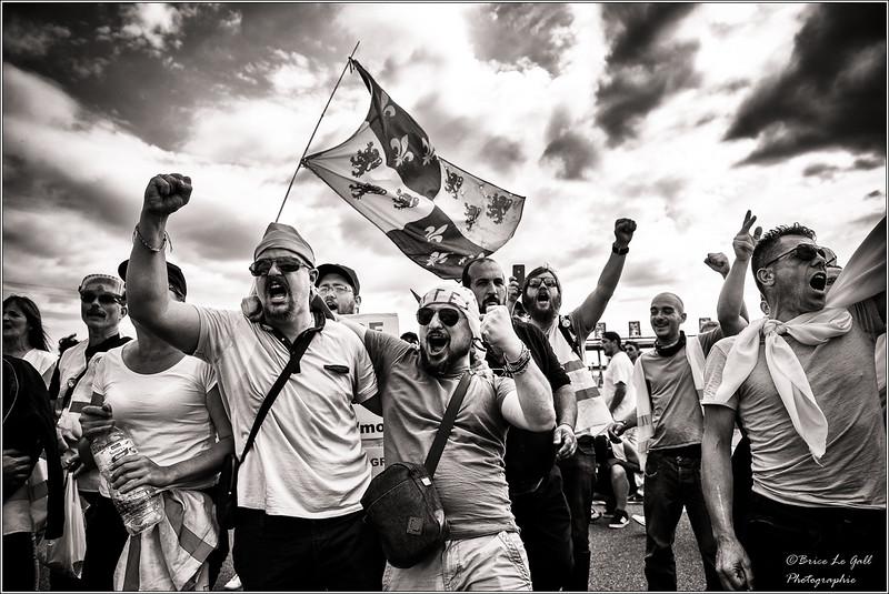 Outre le gilet fluorescent qui a permis de créer un lien entre automobilistes et avec des pans entiers du monde ouvrier, les Gilets jaunes ont su mobiliser un ensemble de symboles en mesure de fédérer au delà des clivages partisans. La Marseillaise, les bonnets phrygiens, les cahiers de doléances réactivent l'imaginaire de la Révolution française. Les drapeaux tricolores et régionaux qui rappelent au gouvernement que son pouvoir n'est rien sans le consentement du peuple permettent de neutraliser les différences, de symboliser son unité. Ils permettent à tout un chacun de se rattacher à une histoire collective, de s'identifier à un « nous » valorisé et valorisant, en particulier pour celles et ceux qui ne disposent guère d'autre formes d'intégration et de reconnaissance que le sentiment d'appartenance nationale. <br /> <br /> Péage de Chamant, Senlis, Juin 2019.