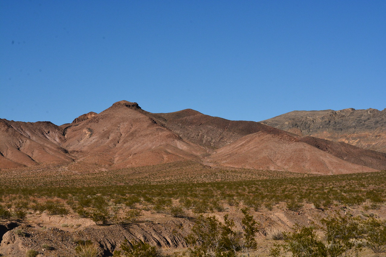 Looking back,  Me thinks Shoshone Peak is peaking our behind the large red bump left of center.