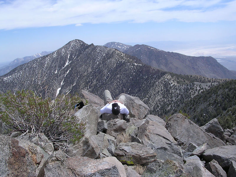 Ryan sacked out on the summit of Mount Inyo. His knee pointing to Keynot Peak.