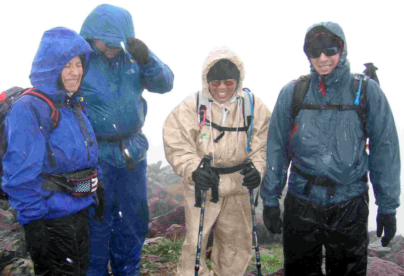 On the summit of Monument Mountain. It's raining, hailing and windy, but we are happy to be here. I'm wearing sunglasses to protect my eyes from the hail. (Photo by Ron)