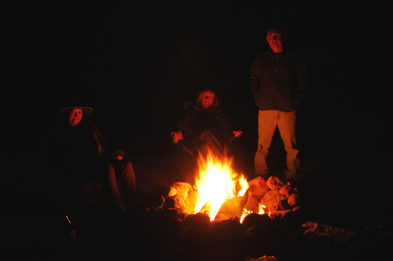 Group shot by campfire light.