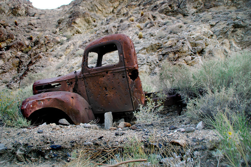 Old truck along side the road.
