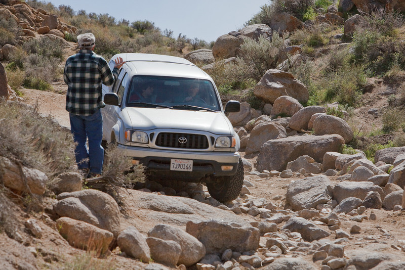 Bill giving directions<br /> <br /> It is impossible to see over the hood to guide the tires precisely over the rocks. It takes a lot of faith to just blindly follow directions!