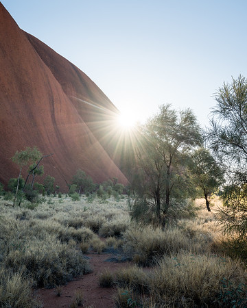 The sun peeks over the side of Uluru, Australia.