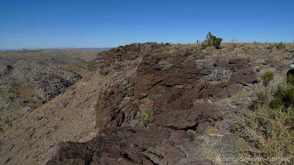 Looking at the summit plateau from the edge - we climbed up in those rocks somewhere. See Robin just to the left of the bush for perspective.