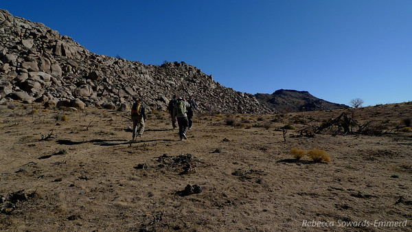 We head along the base of a boulder-covered hill.