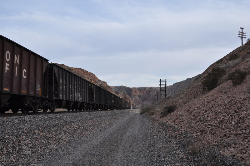 We walk down the mojave road while a train passes by.
