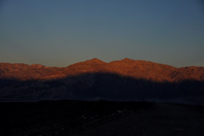 As we drive out of Warm Springs Canyon and back to West Side Road, we watch sunset over the Funerals. The shadow is of the Panamints, the range we've just been playing around in.<br /> <br /> The peak to the left, in the background (with the white splotches on it) is Funeral Peak, the tallest in that range. We climbed that one last year on our Thanksgiving trip.