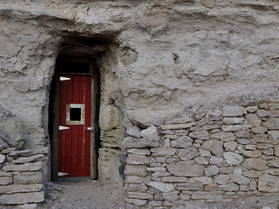 Some of the doors were brightly colored, standing out against the dull grey rock.