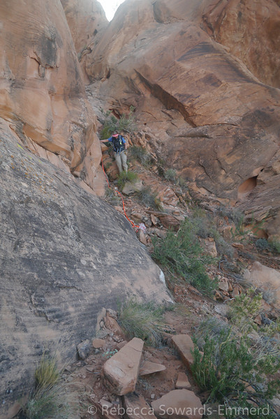 At the base of the canyon we had the option of a ~20 ft rappel, or scrambling over the ridge to this steep descent and crossing some steep friction slabs. We decided to check out the slabs to see how wet they were before setting up the rappel.