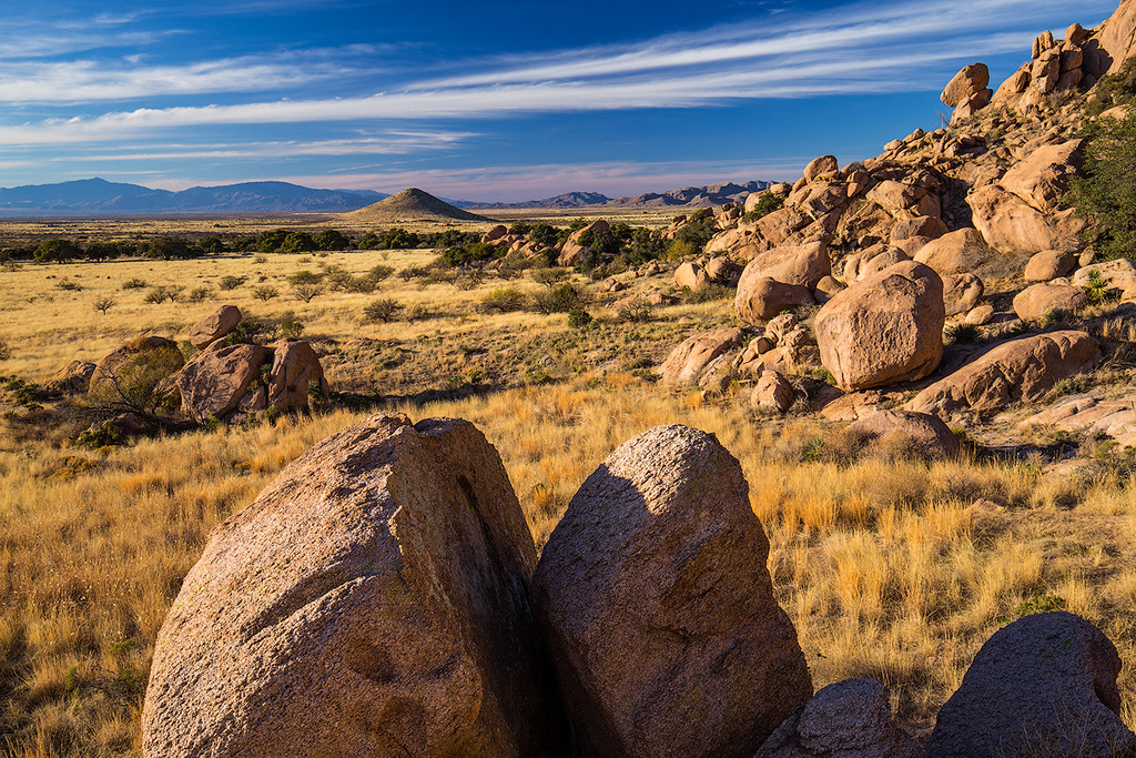 Granite boulder transition into grasslands on the western slopes of the Dragoon Mountains. Rincon Mountains in the background.