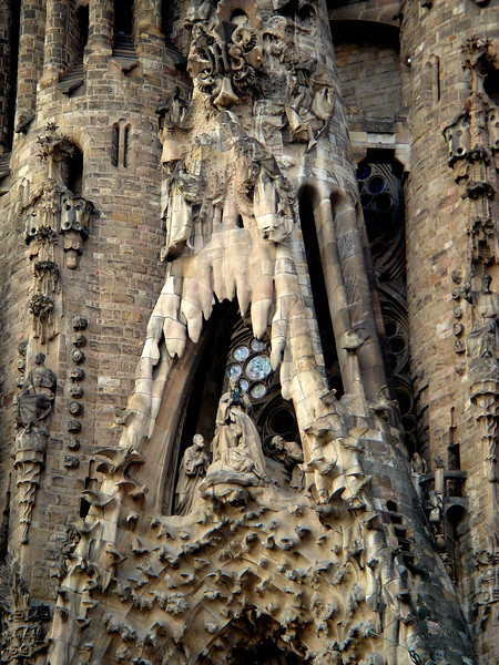 Temple of the Sagrada Familia by Gaudi - Close up of the NATIVITY FAÇADE on <br /> <br /> Gaudi's design style is eclectic, with obvious Neo-Gothic, Art Nouveaux and wild imagination elements thrown in.<br /> <br /> The Sacred Family Church will have 12 spires soaring as high as a modern 35-story building, So far 8 have been built (including the 4 shown in the photo). In addition, there will be a central dome and spire rising yet another 15 stories.