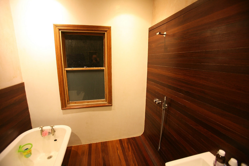 environmentally sustainable bling -  hardwood (FSC cumaru) wet room, waxed polished plaster wall with refurbished original bath and window