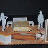 Act 2: Rm 39 Hotel Ultima.<br /> Sofa is folded out to bed (mesh on headboard to aid audience visibility!) Extra side table added so there is a bedside table either side. Orange pillows, yellow/orange floral bedspread. Blue rug changed for orange one. Seat cushions removed from bentwoods. Coloured tablecloth added to table. Ottoman uncovered (padded orange seat cushion on top). Painted semi see-through gauze screen. Could have set dressing of bedside lamps, different phone?