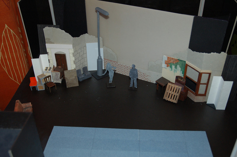 Screen set at an angle; furniture piled in front of flats either side of stage; wall across bottom of screen; streetlamp to one side of screen. Flats show door (with flip down sign above) for co-op bank scene (door not practical); door in stone wall opens to reveal phonebox interior; half painted wall for decorating scene; window flat (lower half of window raises up like a sash) for breaking into the squat.