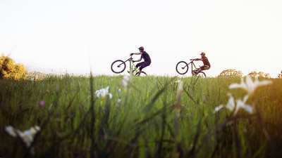 Two friends riding mountain bikes doing wheelies through the grass during the Spring Time in Sonoma County, CA