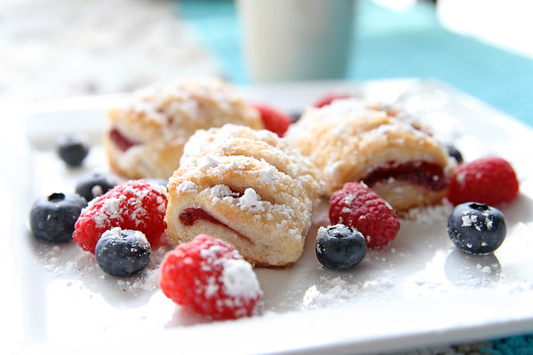 Raspberry pastries with blueberries and raspberries on plate