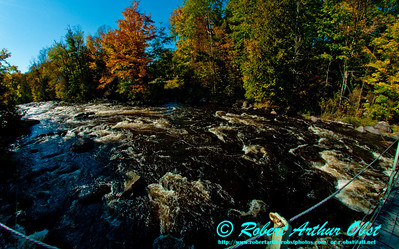 Blue skies and autumn colors frame Boy Scouts Rapids upstream of the second suspension bridge on the wild Wolf River within northeastern Wisconsin and the Gardner Dam Scout Camp near White Lake (USA WI White Lake)