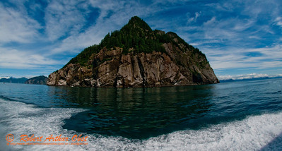 Towering cliffs guard Blying Sound of the Pacific Ocean under blue skies within Driftwood Bay State Marine Park southeast of Seward on the Kenai Peninsula (USA Alaska Seward)