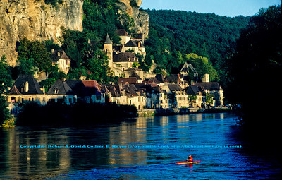 Bob Obst kayaking past Les Plus Beaux Villages de France La Roque Gageac highlighted by gorgous evening light within the Dordogne River Valley (Europe France Limousin Périgord Dordogne River Valley La Roque Gageac; Obst Hayes FAV Photos 1990 DWS River Valley Dordogne Scanned Image 0026)