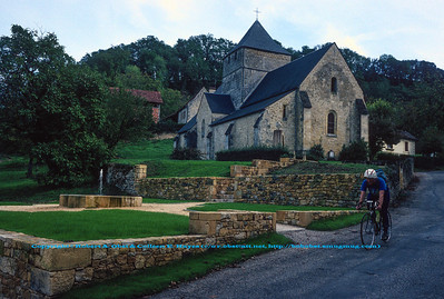 Bob Obst bicycling past historic monument Église Notre-Dame de l'Assomption d'Aillac at Carsac-Aillac within the Dordogne River Valley (Europe France Limousin Périgord Dordogne River Valley Carsac-Aillac; Obst Hayes FAV Photos 1990 DWS River Valley Dordogne Scanned Image 0004)