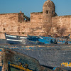 Traditional painted blue wooden fishing boats fill the harbor below the turret of the old fortress in Essaouira, Morocco