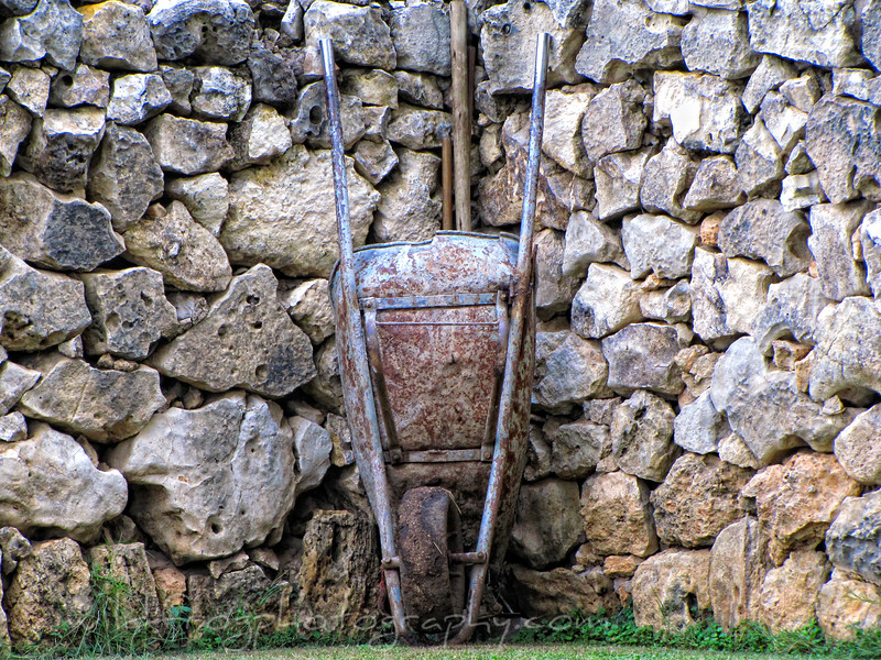 wheelbarrow leaning against a stone wall