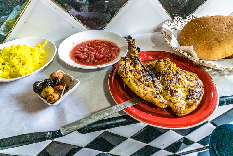 Moroccan street food featuring grilled chicken with olives.