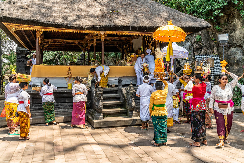 Balinese women in traditional clothing, carrying baskets on their head at Goa Lawah temple""