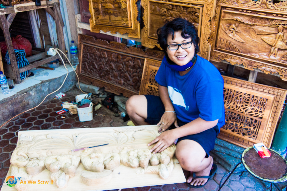 A wood carver creating a wooden relief in Tanah Lot village.
