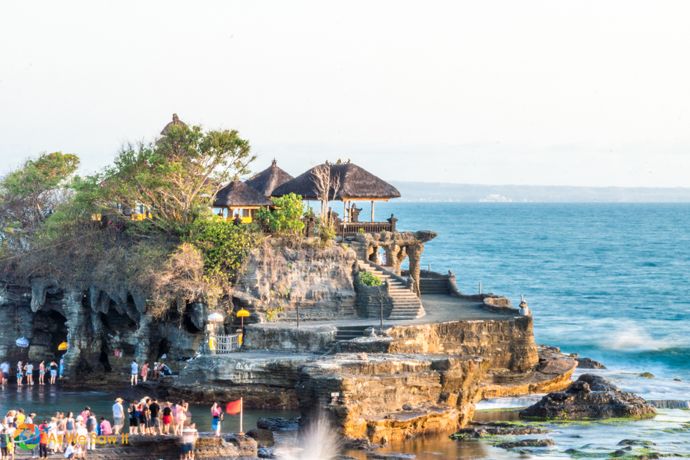 Pura Tanah Lot during low tide with visitors waiting to go inside.