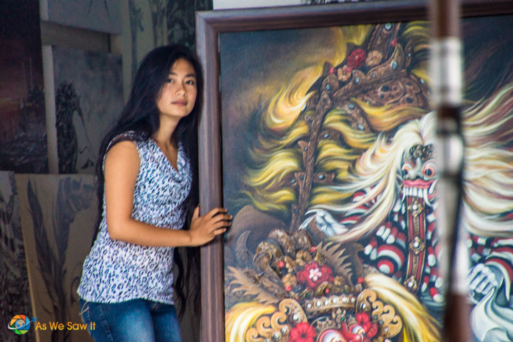 Indonesian woman stands next to a painting at an art stall in a Bali market