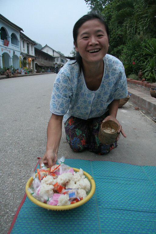 Local woman demonstrating how to give alms to the monks.