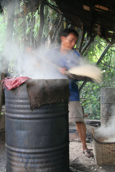 Man scooping sticky rice into vats to ferment