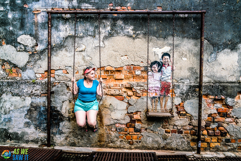 Penang street art is interactive. You can sit on a swing with kids drawn on the other one. One of the most unique places to visit in Malaysia.